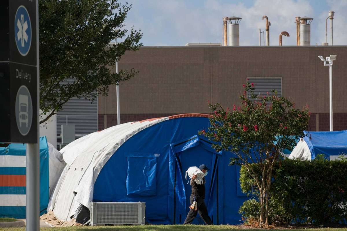 A construction crew works to setup tents in case of overflow COVID-19 and ICU patients outside Lyndon B. Johnson Hospital on Monday, Aug. 9, 2021, in Houston
